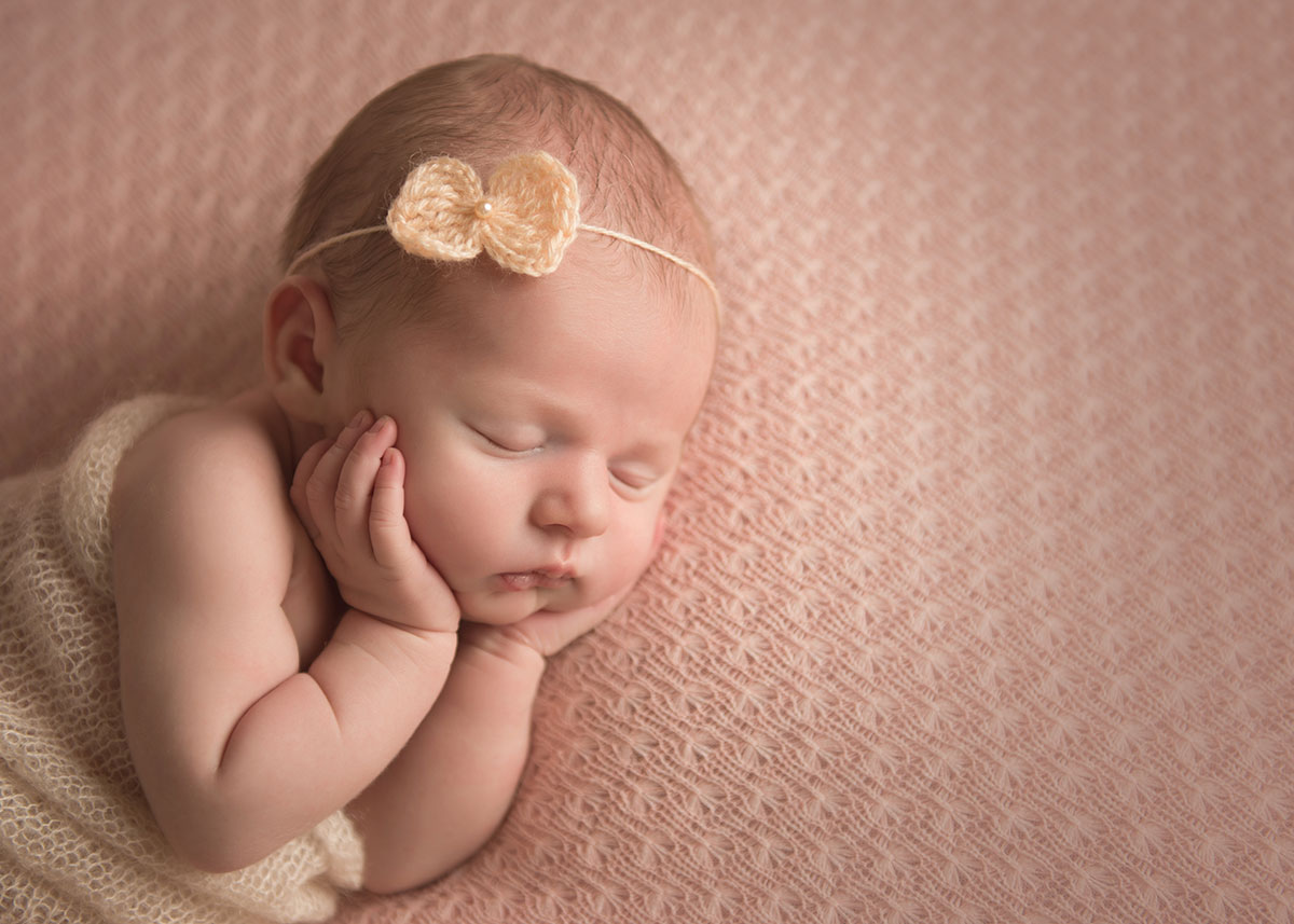 Infant girl sleeping with her hands on her cheeks
