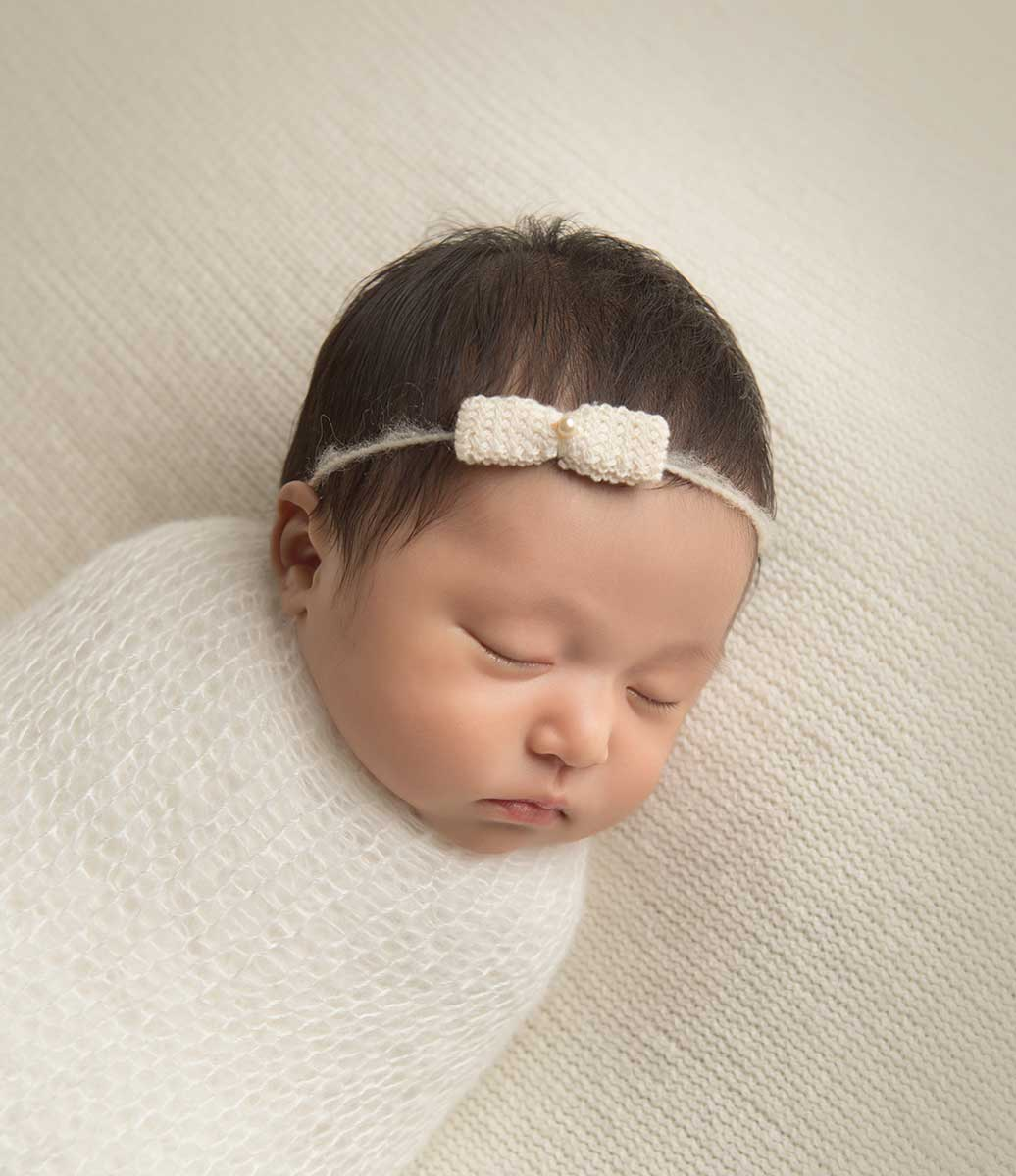 Cute newborn girl wearing a headband sleeping on a white blanket