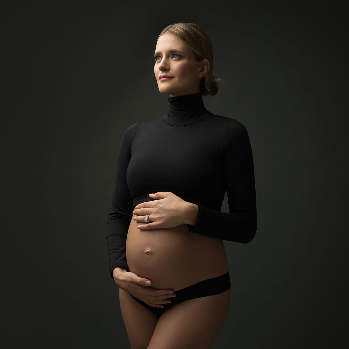 Pregnant woman cradling her belly for a maternity portrait