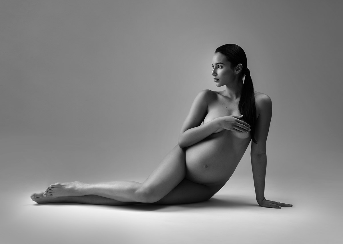 Pregnant woman laying on her side at a NYC maternity photo studio