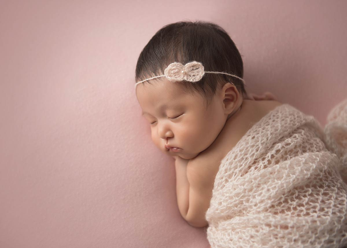 Cute baby girl sleeping with a headband on a pink blanket