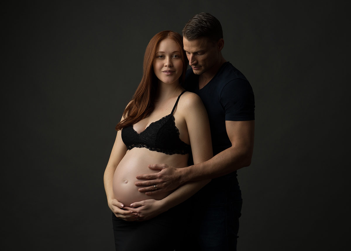 Joyful father supporting his pregnant wife at a NYC maternity photo studio