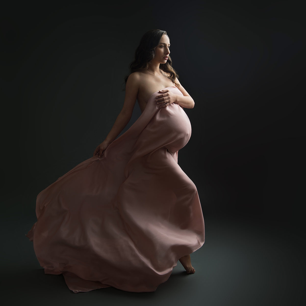 Maternity model holding a flowing dress while posing at a NYC maternity photo studio