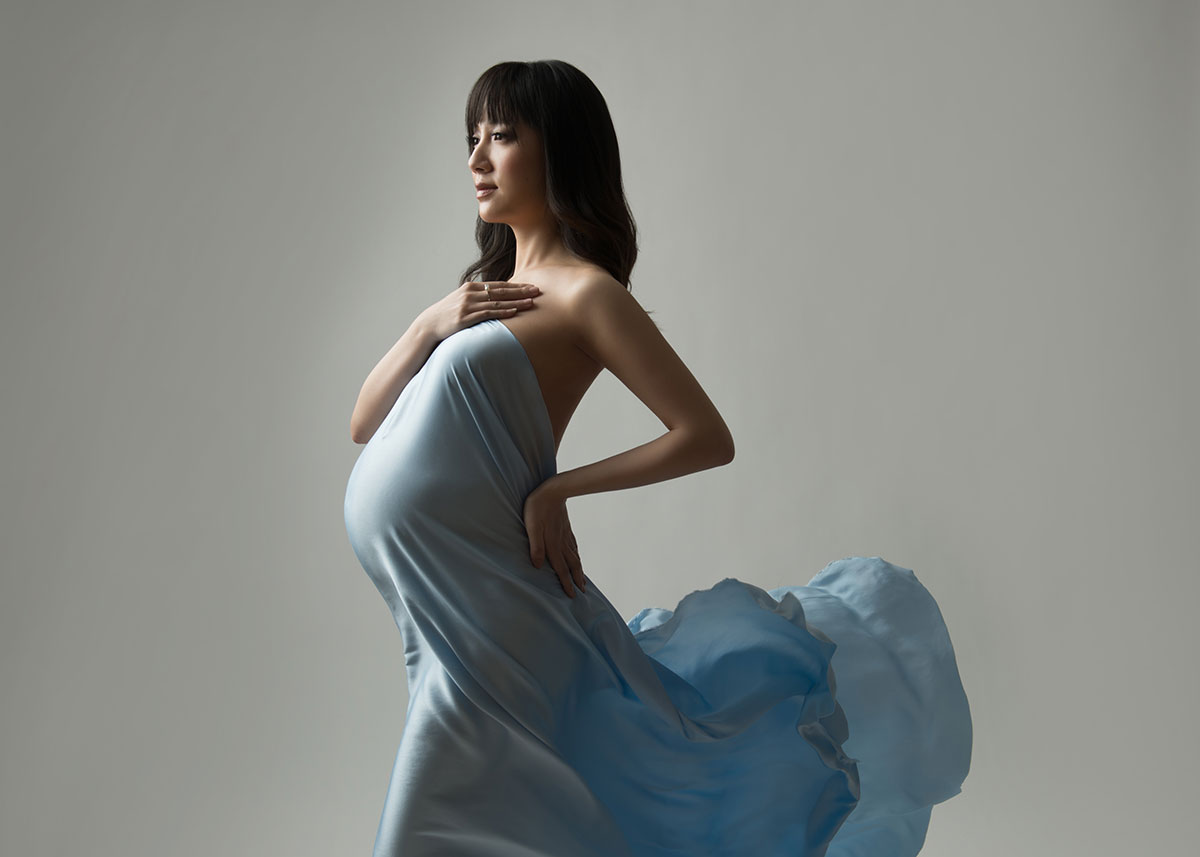Blue cloth draped over a pregnant woman