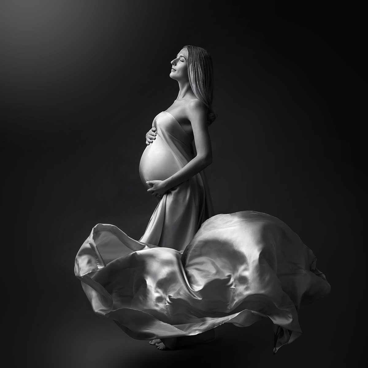 Artistic black and white photo of a woman wearing a flowing maternity fabric