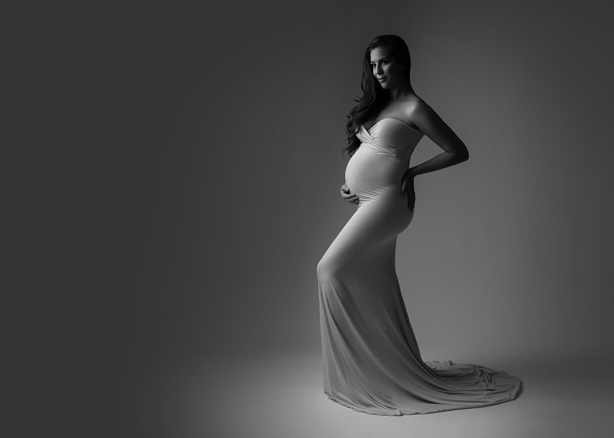 Tasteful black and white photo of a woman in a long dress posing for her maternity portrait