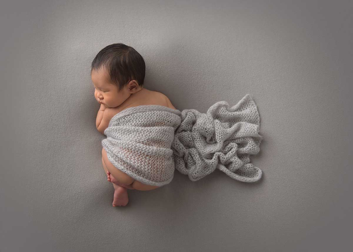 Newborn photo of a baby sleeping on a gray blanket