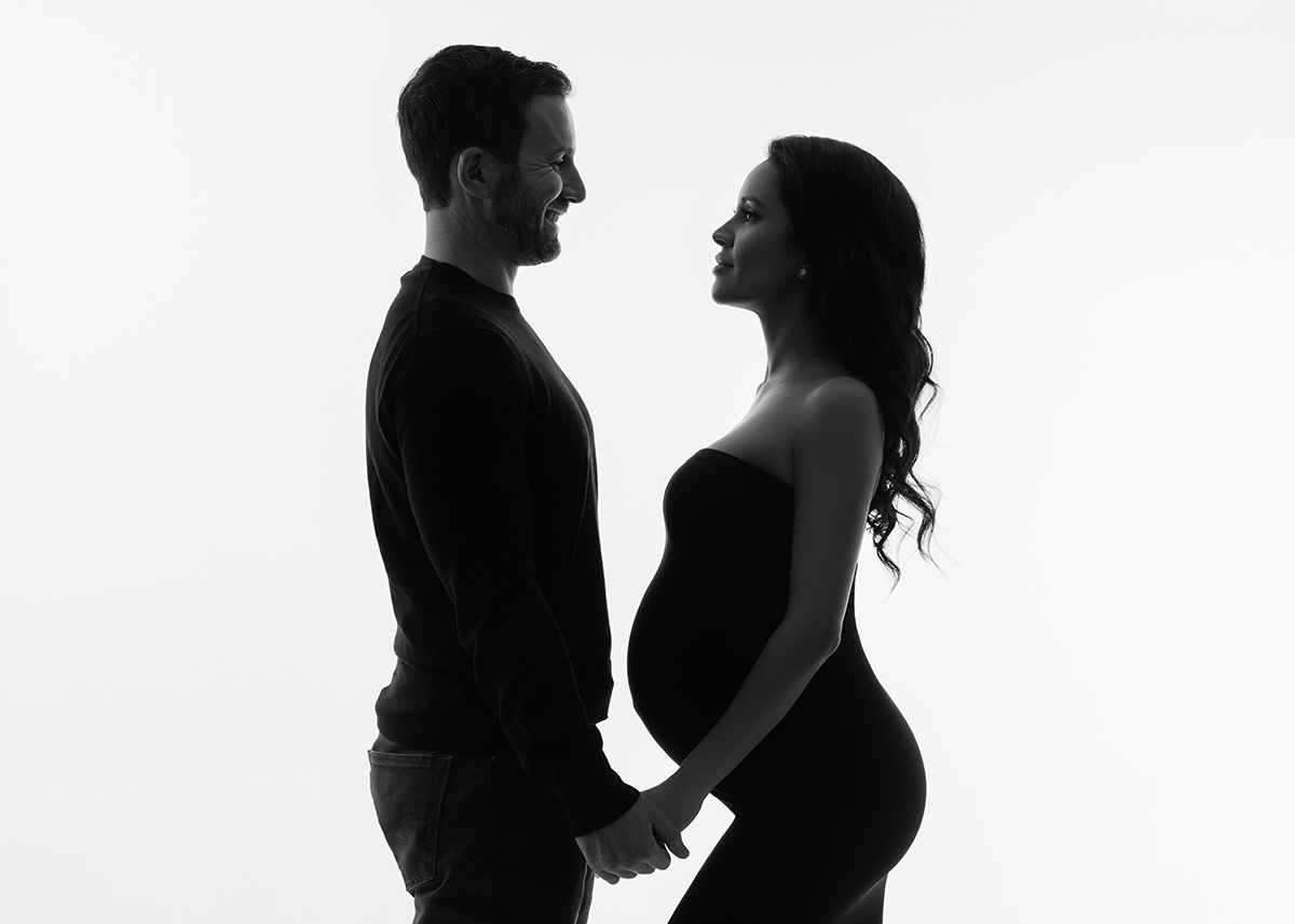 Man and woman posing for a couples maternity portrait at a NYC photo studio