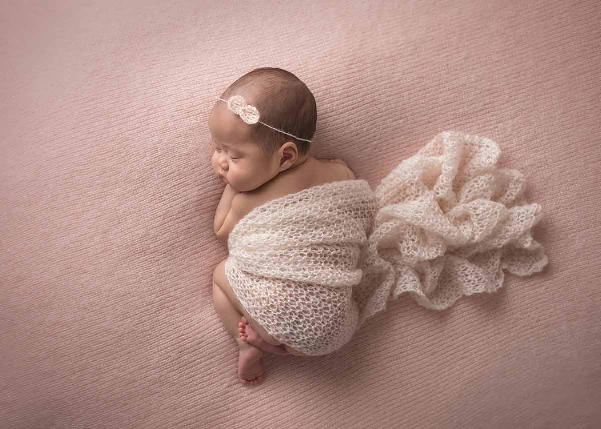 Top down view of a sleeping newborn baby on a blanket at a NYC photo studio