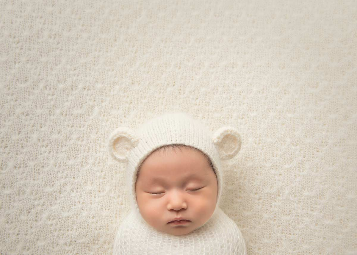 Top down photo of a newborn baby with a hat