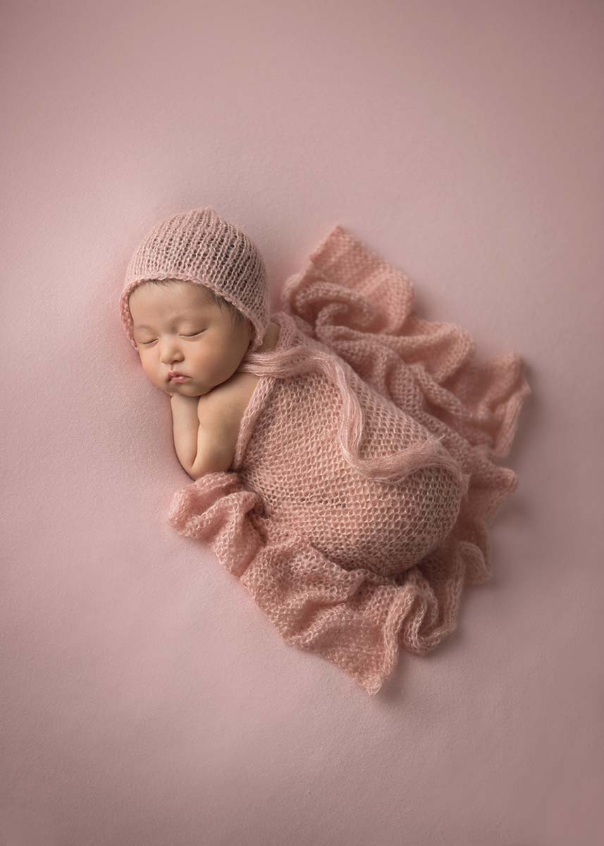 Cute newborn baby sleeping on a pink blanket in NYC