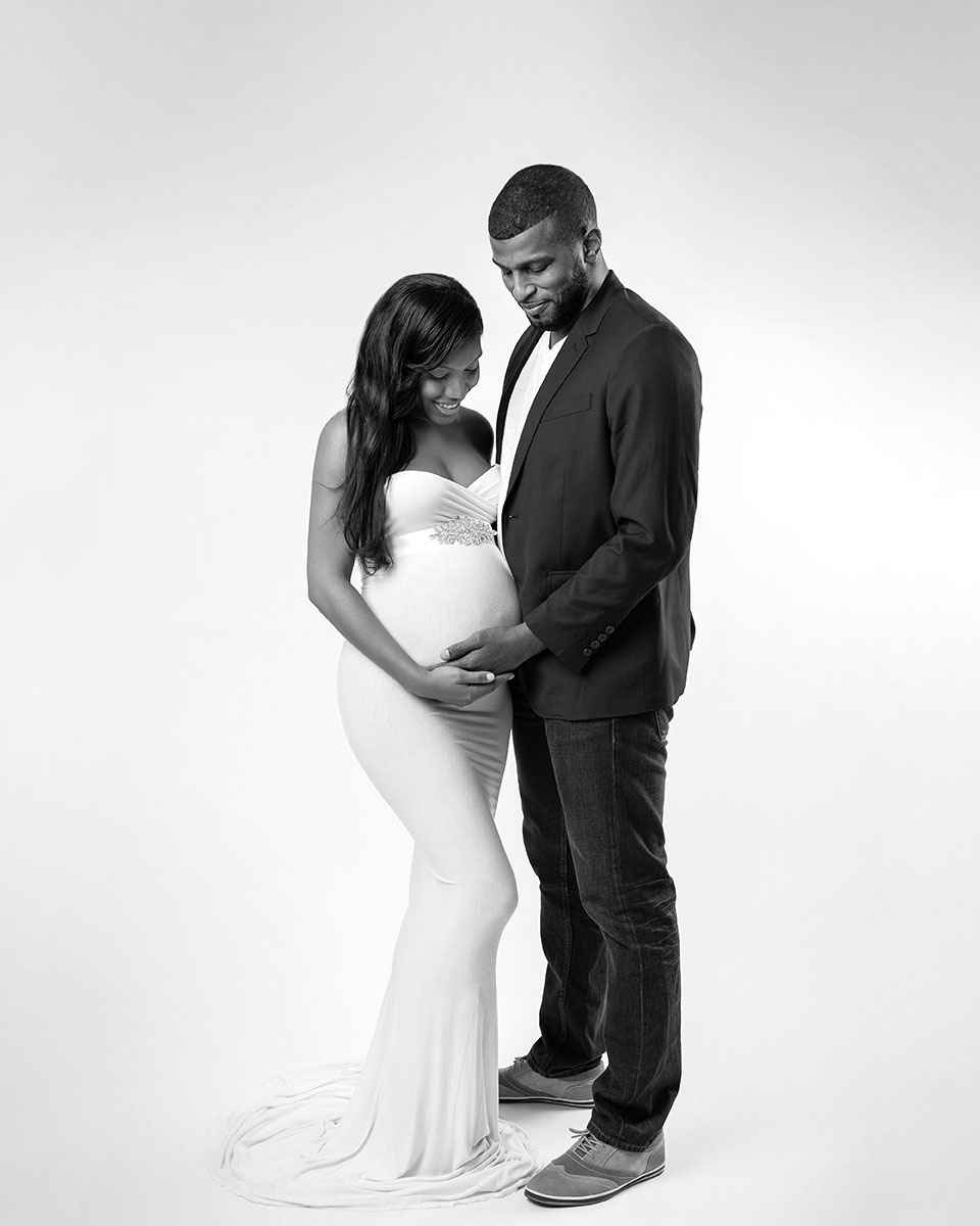 Married couple posing for a maternity portrait in a NYC studio