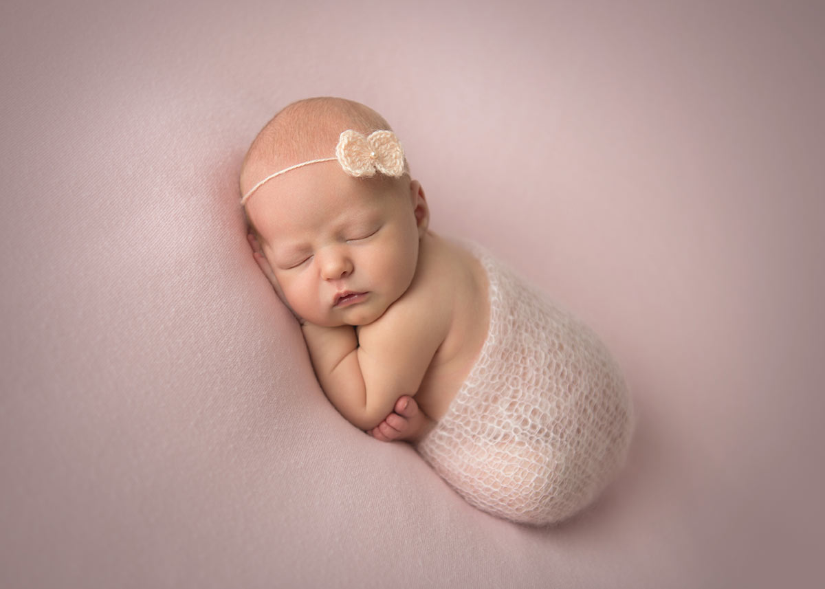 Infant baby swaddled in a knit and wearing a headband while posing for a newborn photo in NYC