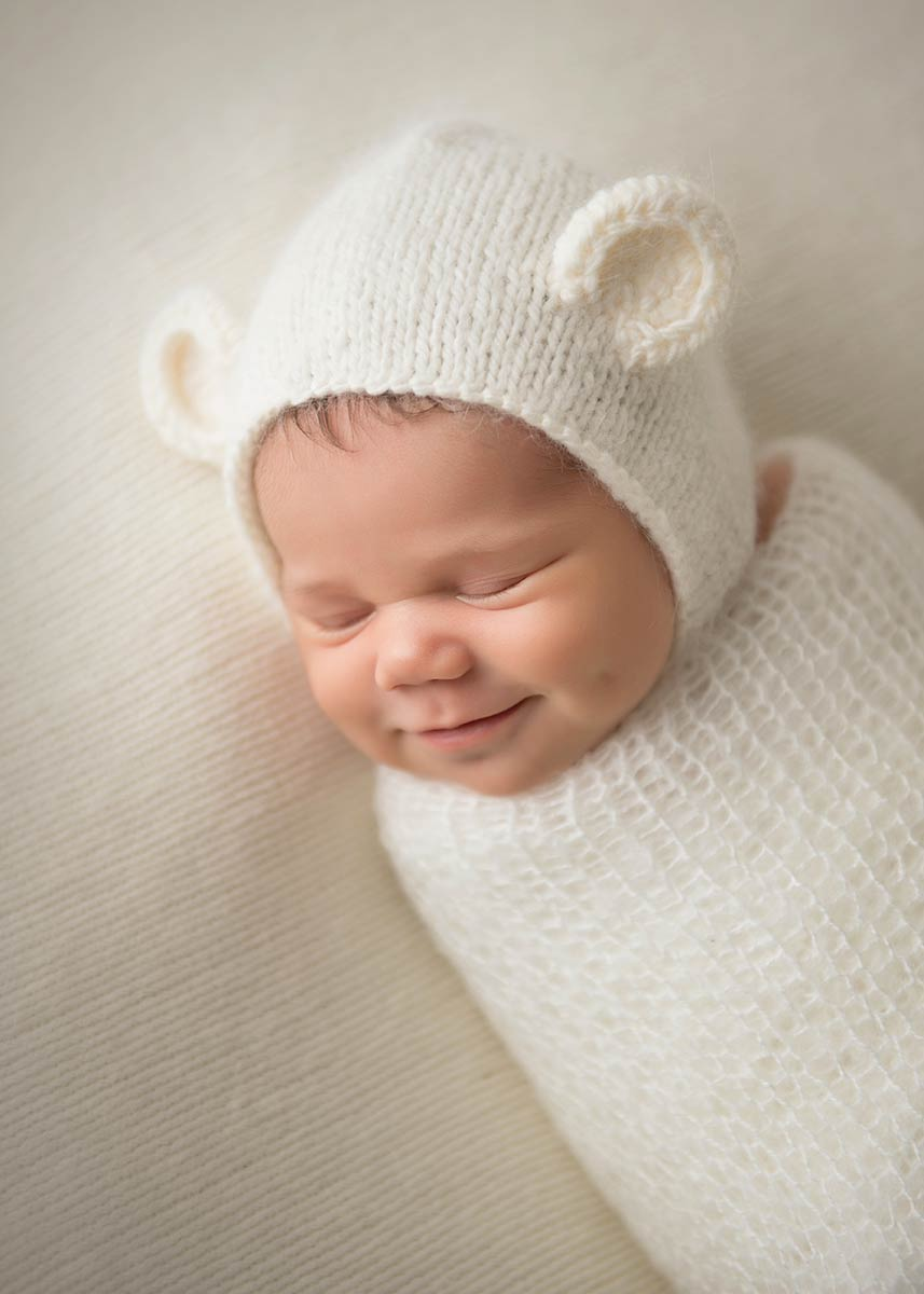 Beautiful newborn photo of a baby smiling wide