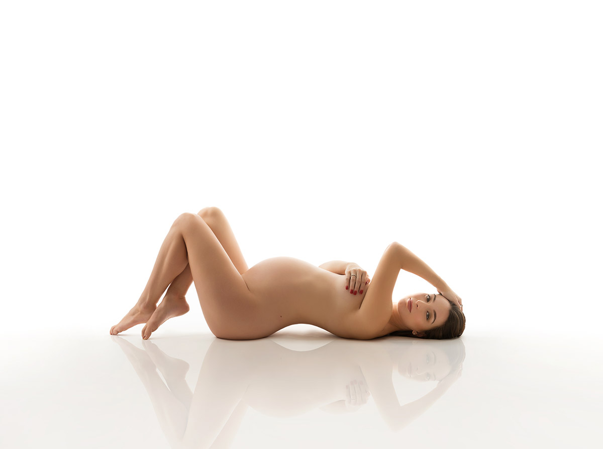 Nude maternity photo of a woman laying on her back and looking at the camera
