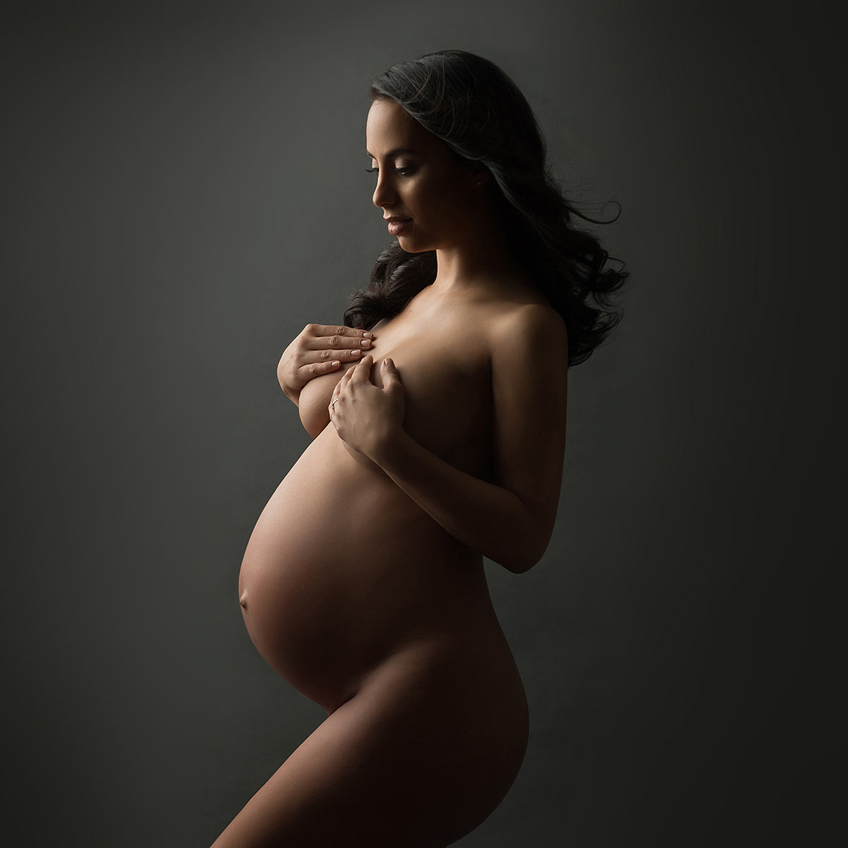 Nude portrait of a pregnant woman covering her breasts