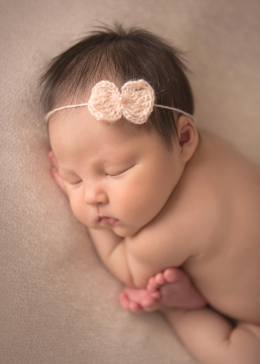 Infant with fuzzy hair posing for a newborn portrait