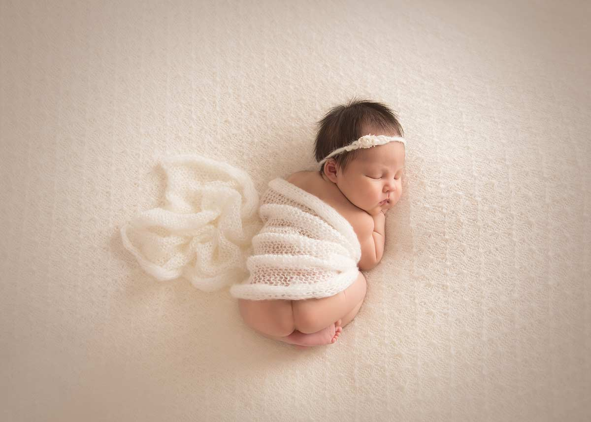 Baby girl sleeping happily on a knit blanket and a cover