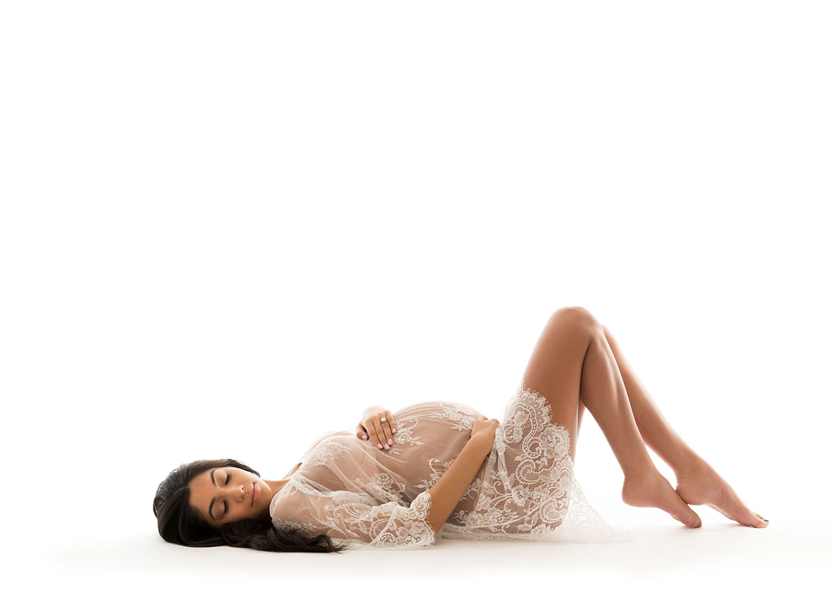 Woman with black hair and white lace laying on the floor in a nyc maternity photo studio.