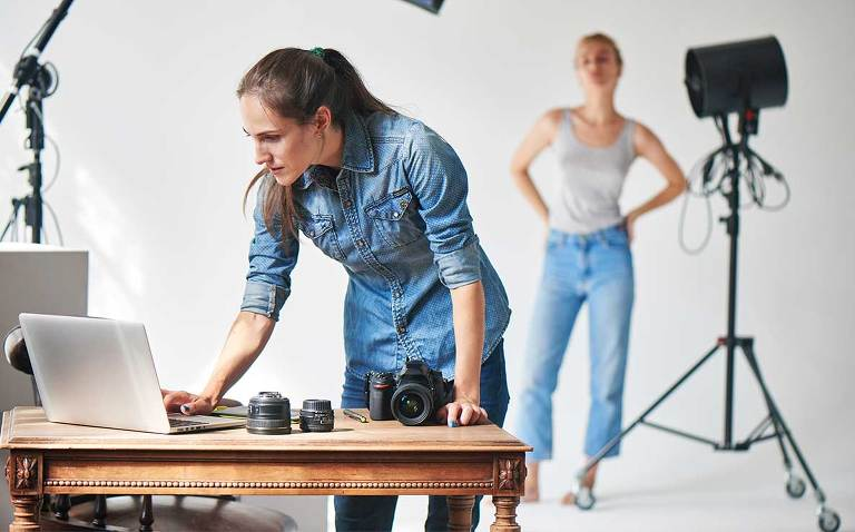 Photographer in a busy studio checking her laptop