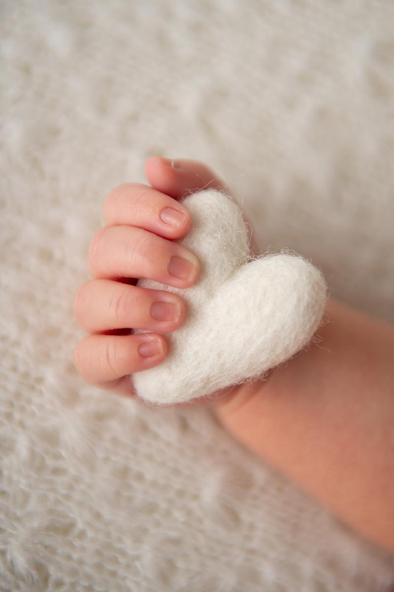 Closeup of infant's hand holding a stuffed heart