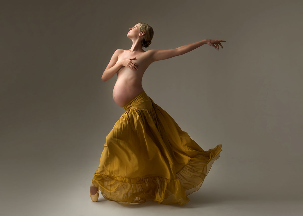Pregnant ballerina in a yellow skirt dancing
