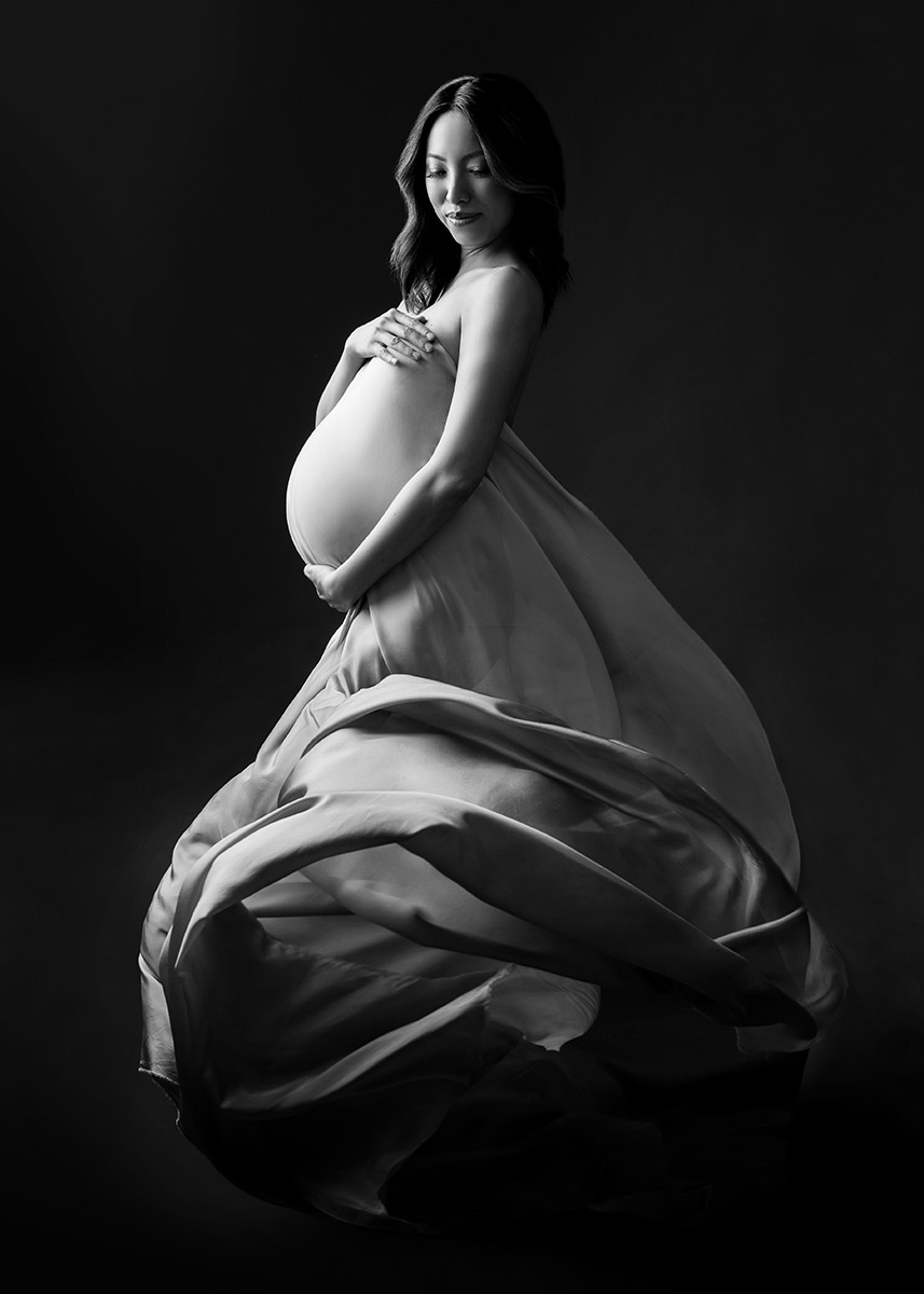 Expectant mother with a flowing dress posing for a photo