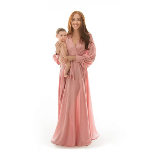 Mother in a beautiful dress holding her baby