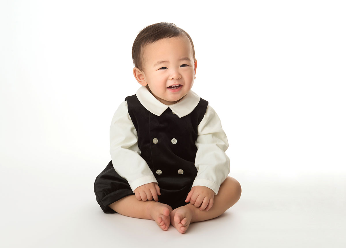 Cute baby boy wearing a stylish outfit sitting in a photography studio