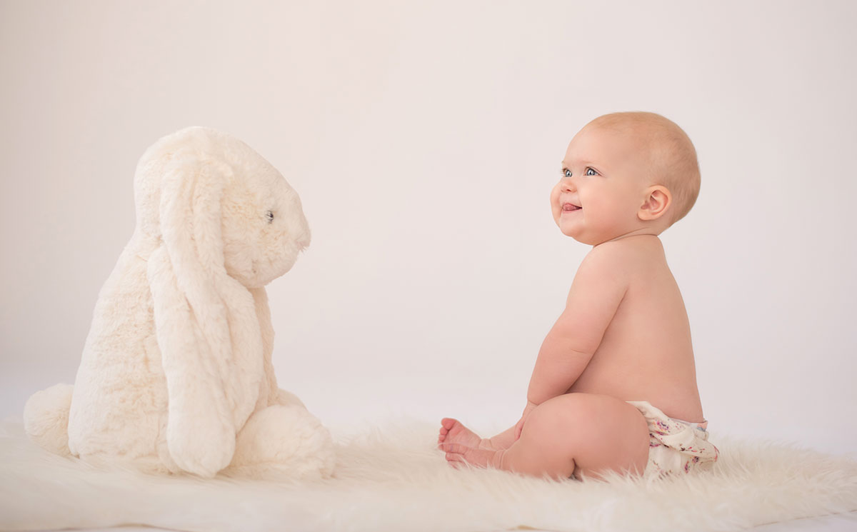 Sweet baby sitting on the floor of NYC photo studio looking at a stuffed toy