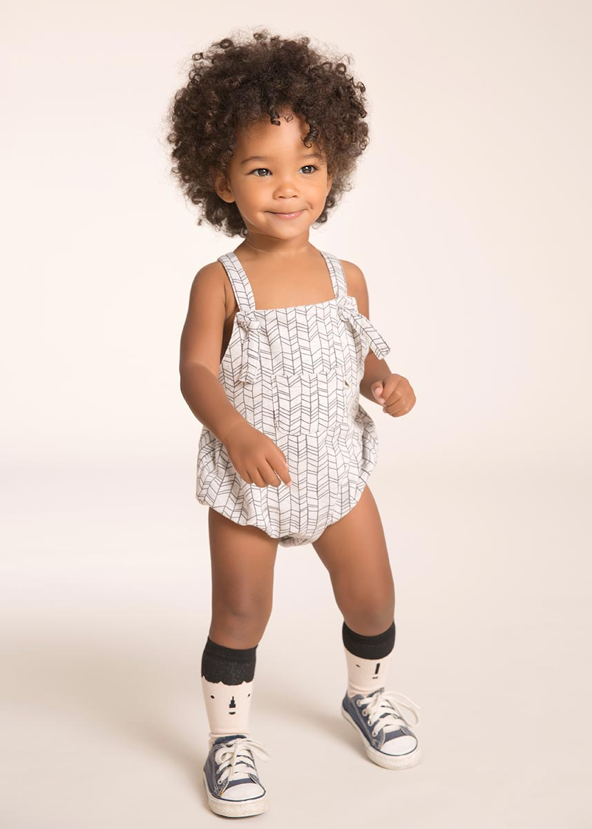 Boy with adorable curly hair wearing sneakers in a photo studio