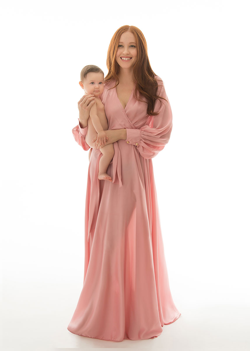Mother with red hair wearing a pink dress holding her baby and smiling at a photography studio