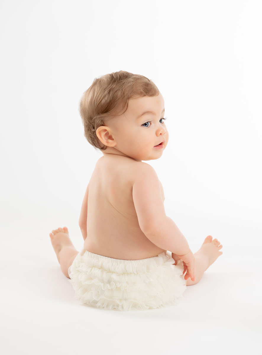 Baby in a diaper cover playing on white