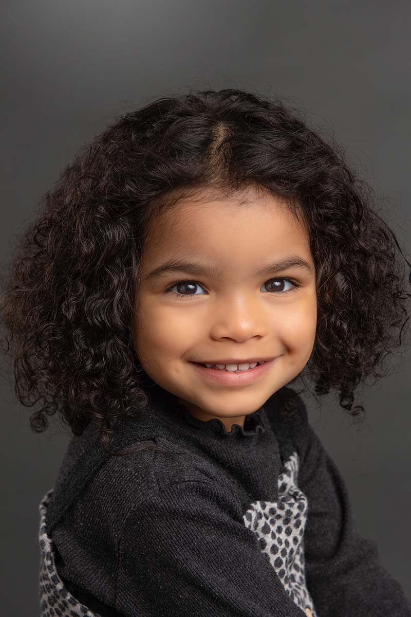 Beautiful girl with curly hair smiling happily at a NYC photography studio