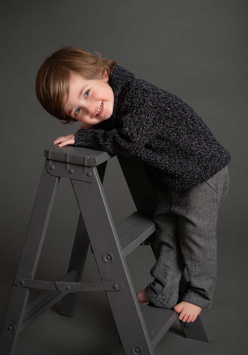 Happy boy playing on a little ladder