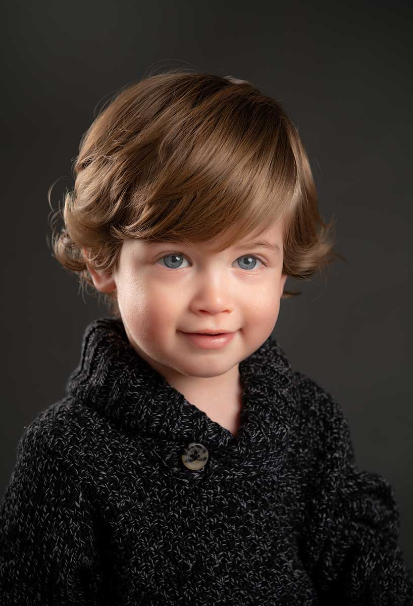 Cute toddler with brown hair and a sweater
