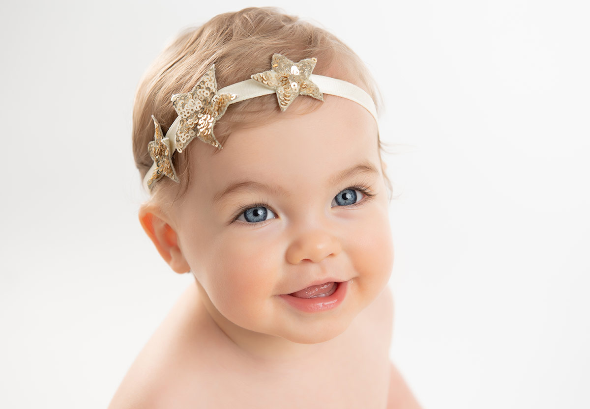 Super cute baby with blue eyes smiling at the camera