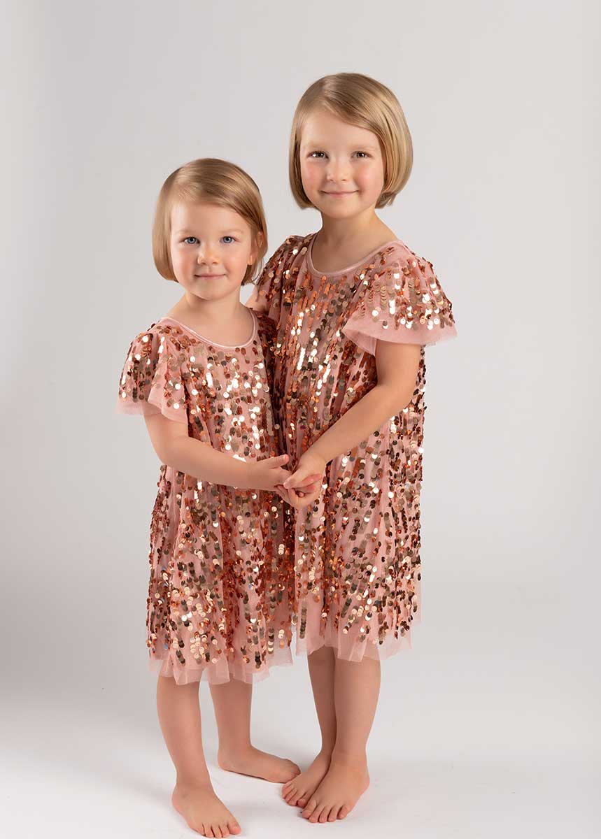 Two adorable sisters in matching dresses posing for a photo