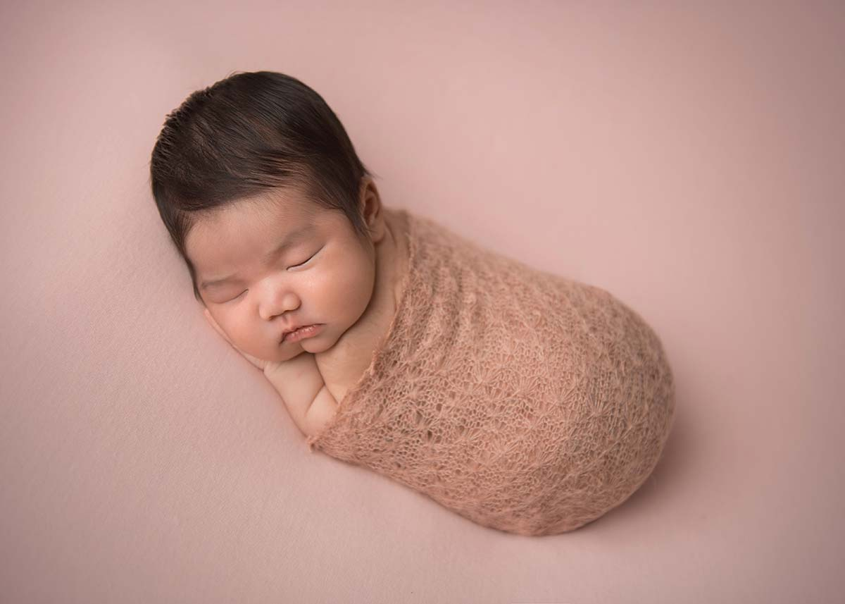 Infant wrapped in a knit blanket