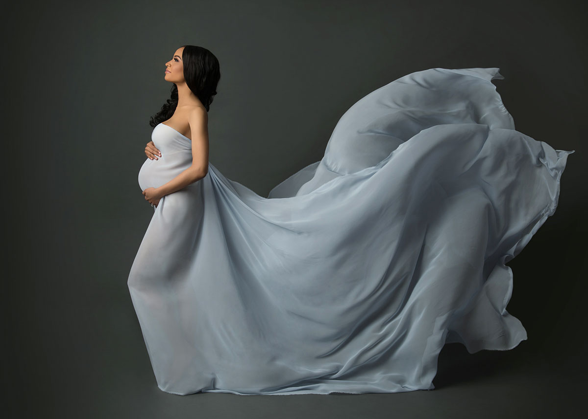 Flying blue fabric on a pregnant model