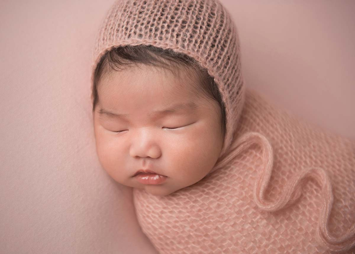 Sweet baby sleeping with a knit hat at a NYC photography studio