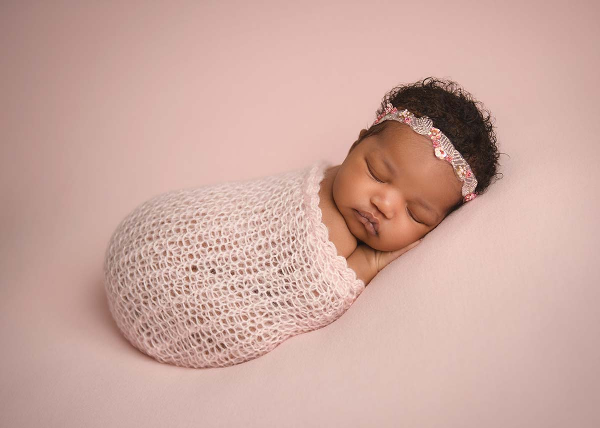 Baby girl wearing a headband and pink swaddle sleeping on a blanket