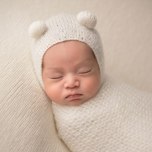 Sleepy infant with a knit hat posing for the camera at a newborn photography studio in NYC