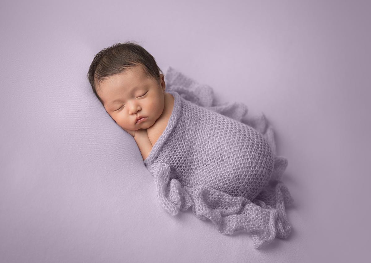 baby sleeping on lilac purple blanket with ruffle knit lavender wrap