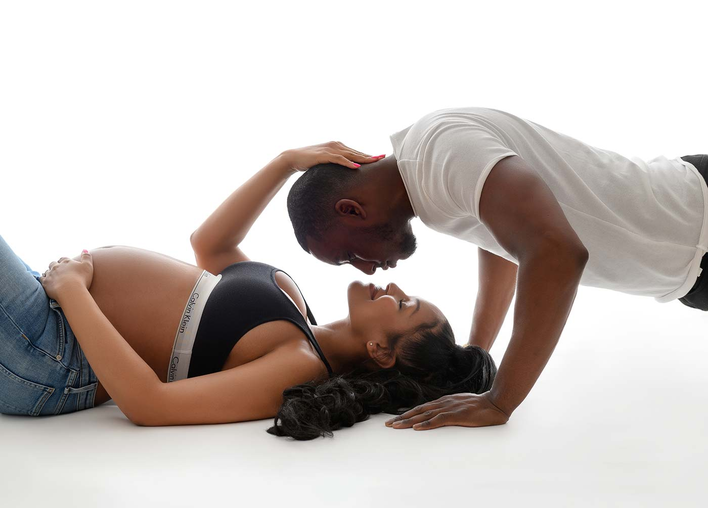 pregnant couple kissing while lying on the floor with Calvin Klein lingerie intimate portrait