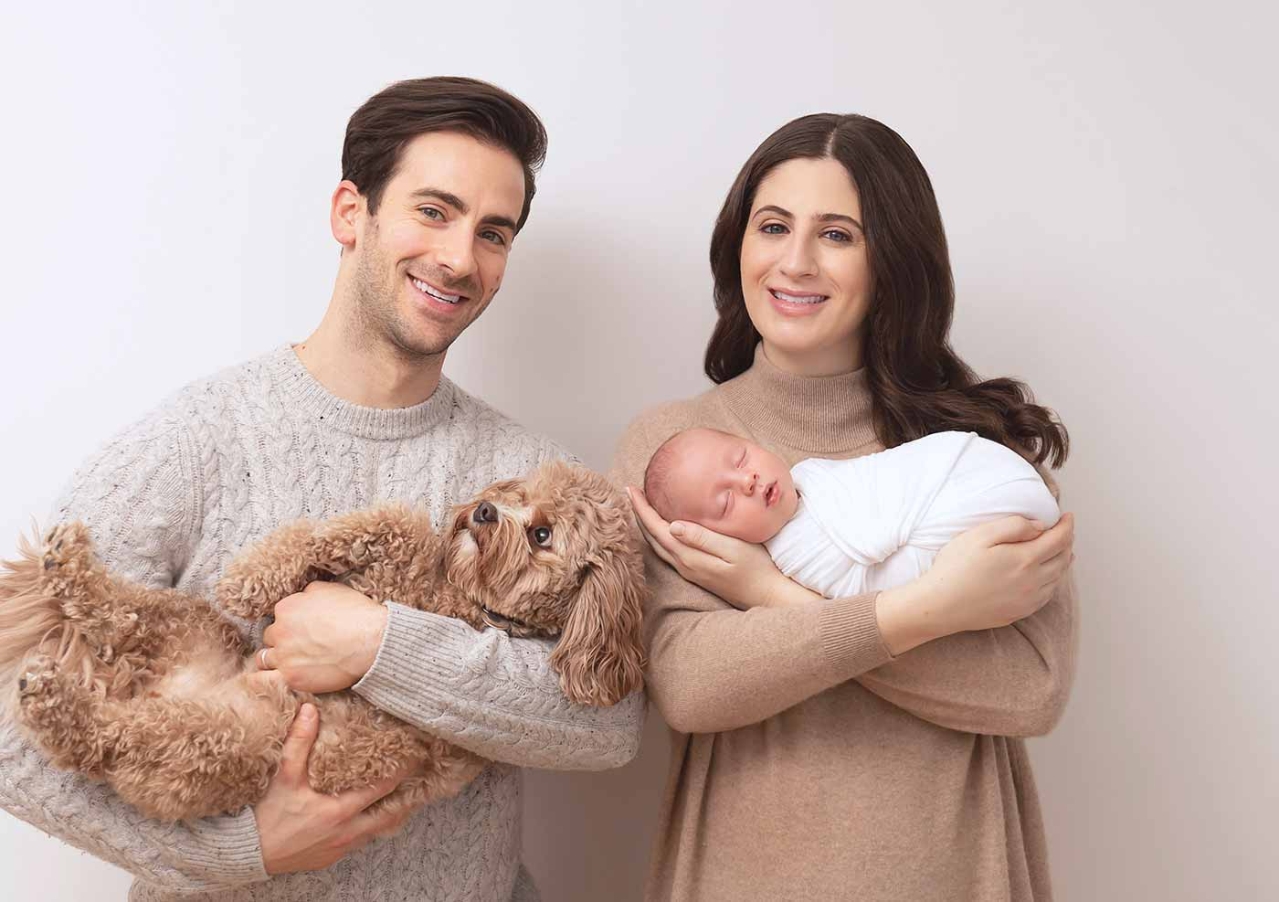 family photo with swaddled newborn and fluffy labradoodle dog